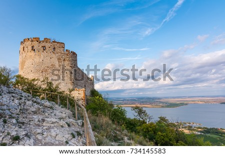 Castle in Palava, Czech republic, ruins of wall, landscape panorama of near village. #734145583