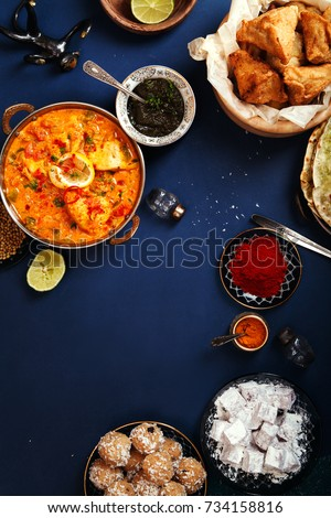 Indian cuisine on diwali holiday: tikka masala, samosa, patties and sweets with mint chutney and spices. Dark blue background. Vertical composition with copy space centered #734158816