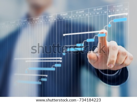 Project manager updating tasks and milestones progress planning with Gantt chart scheduling interface on a virtual screen Royalty-Free Stock Photo #734184223
