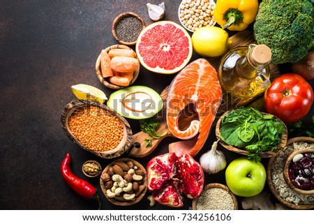 Balanced diet food background. Organic food for healthy nutrition, superfoods. Meat, fish, legumes,  nuts, seeds, greens, oil and vegetables. Top view copy space on dark stone table. #734256106