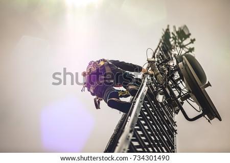 Telecom Worker Climbing Antenna Tower Royalty-Free Stock Photo #734301490
