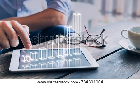 Businessman analyzing growing 3D AR chart floating above digital tablet computer screen, showing successful increase in business profit Royalty-Free Stock Photo #734391004