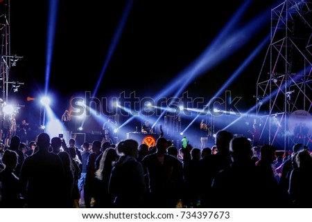 ODESSA, UKRAINE-August 25, 2017: large crowd of spectators, fans of rock concert during music show during day. Spectators in sand of beach during festival of music and sports Z-games. Selective focus #734397673