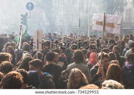 MILAN, ITALY - OCTOBER 13, 2017: Students march in the city streets to protest against the policy of the government on the school, asking  for more rights and protection for their future working life. #734529955