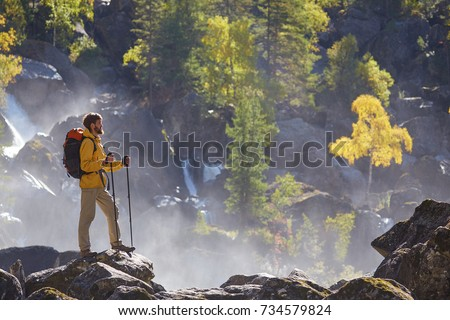 Hiker hiking with backpack looking at waterfall in park in beautiful autumn nature landscape. Portrait of male adult back standing outdoor. #734579824