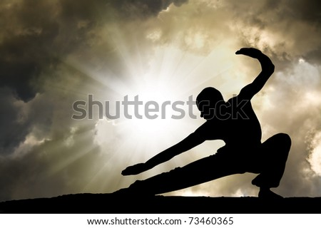 Man Practises Martial Arts with Dramatic Cloudy Sky in Background Royalty-Free Stock Photo #73460365