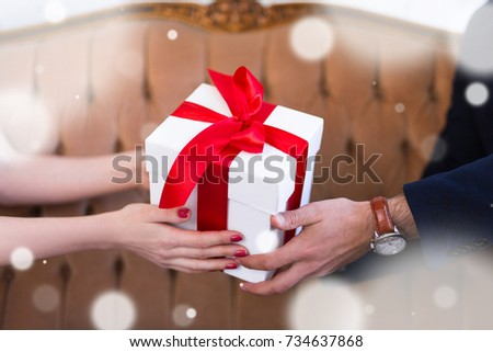 Valentine's day or christmas concept - gift box in male and female hands with falling snow flakes #734637868