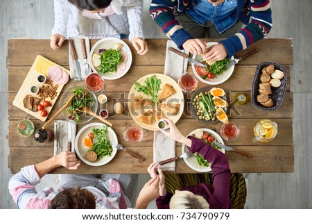 Top view of four people eating delicious food at festive dinner table  in cafe or restaurant celebrating holiday #734790979