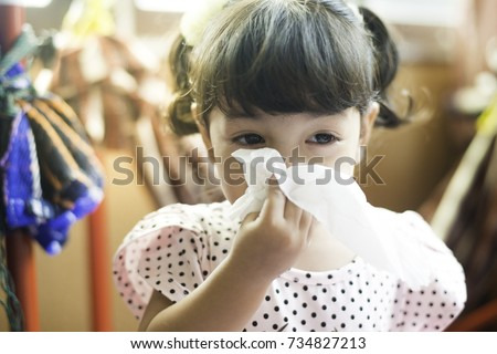 Asian little girl with handkerchief. Sick child  has runny nose. #734827213