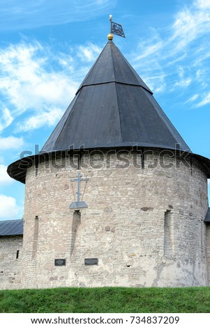 Towers and walls of the fortress of Holy Dormition Pskov-Caves Monastery in Pechory, Russia. Izborsk Tower with decorative weathervane and cross on wall. #734837209