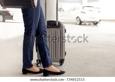Woman tourist standing with luggage waiting for taxi at airport #734852515