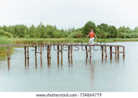 A man doing yoga on wooden pier at the lake #734864779
