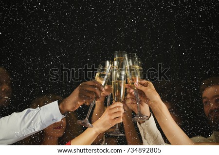 Christmas party time. Young people toasting with champagne flutes. Multiethnic friends congratulating each other with new year. Celebration and nightlife concept, holiday background, selective focus #734892805