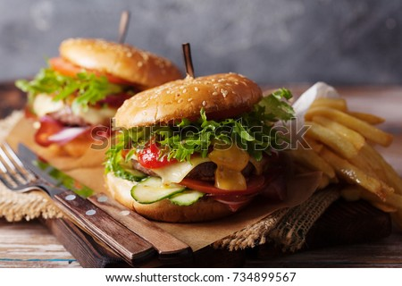 Fresh grilled beef burger and french fries on a rustic wooden table #734899567