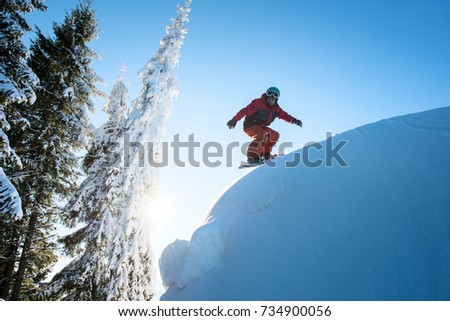 Freeride snowboarder riding on dangerous slope. Blue sky and sun on the background copyspace #734900056