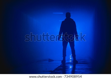 Silhouette standing man in the darkness. Blue background. #734908954