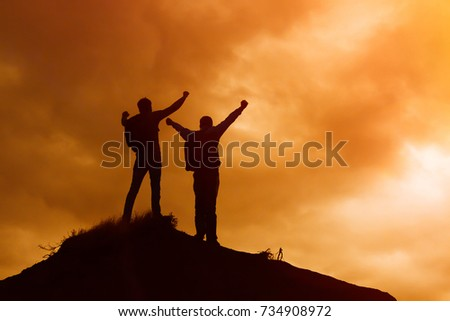 Silhouette of men standing on the top of a hill. #734908972