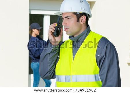 male builder in hardhat with walkie talkie #734931982