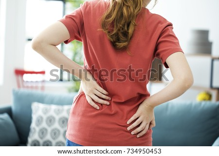 Young woman with back pain #734950453