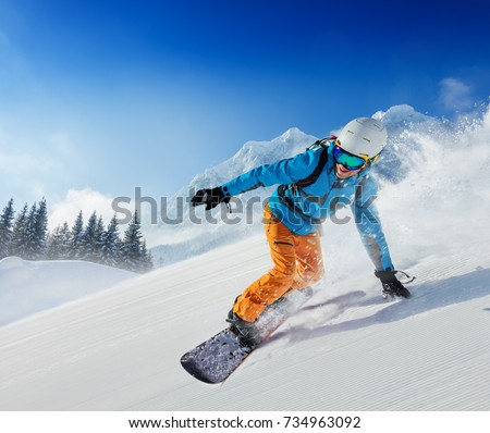 Young man snowboarder running down the slope in Alpine mountains. Winter sport and recreation, leisure outdoor activities. #734963092
