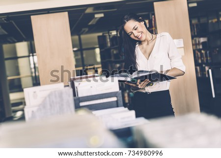 Beautiful woman reading books in a library #734980996