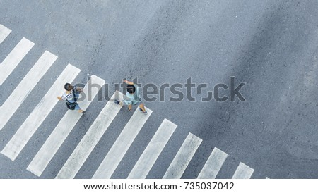 the From the top crosswise view of people walk on street pedestrian crossroad in the city street ,bird eye view. #735037042