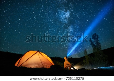 Man tourist with flashlight near his camp tent at night under a sky full of stars. Orange illuminated tent. Royalty-Free Stock Photo #735110275