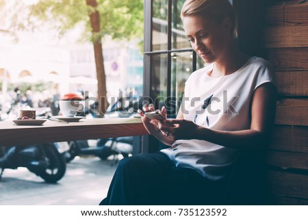 Young gorgeous lady chatting on her smart phone while relaxing in cafe after walking during summer weekend, attractive woman reading text message on cell telephone while sitting in cozy coffee shop #735123592