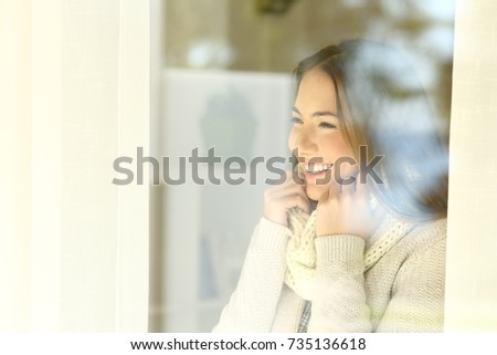 Happy woman warmly clothed looking outside through a window in winter at home or hotel room #735136618