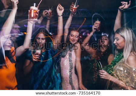 New Year dance party in night club. Happy friends company with drinks, Christmas celebration in motion. Disco people in blurred colors, modern youth life Royalty-Free Stock Photo #735164170