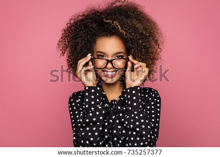 Beauty portrait of a young black healthy woman holding glasses and looking at camera  #735257377