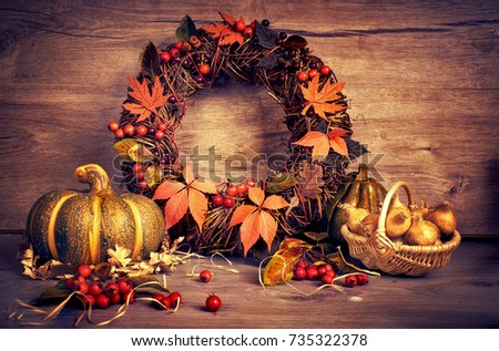 Autumn wreath and still life with pumpkin and onions on wood. Happy Thanksgiving design. This image is toned.