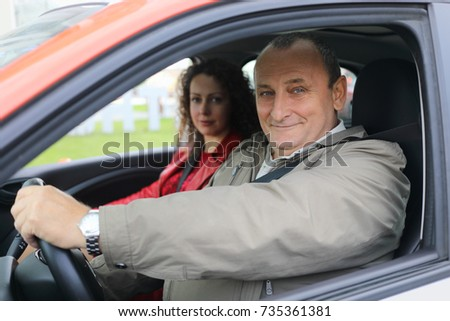 Woman and elderly man fastened with seat belts sit in car, focus on man #735361381