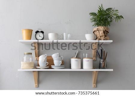Utensils and mugs on shelf Royalty-Free Stock Photo #735375661