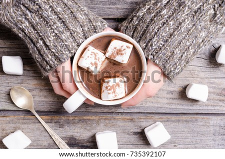 Hot chocolate with marshmallow in woman hand and sweater Royalty-Free Stock Photo #735392107