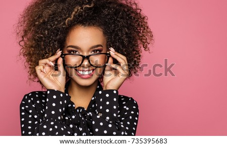 Beauty portrait of a young black healthy woman holding glasses and looking at camera  #735395683