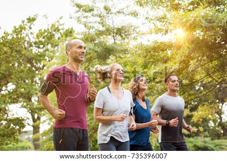 Runners team on morning training together. Group of mature athletes running outside in the park. Group of senior healthy people running outdoor and doing fitness exercises in summer. #735396007