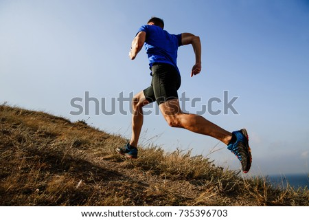 dynamic running uphill on trail male athlete runner side view #735396703