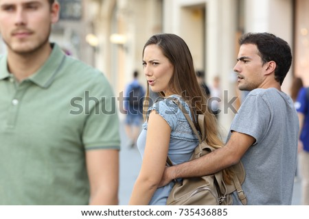Disloyal woman looking another man and her angry boyfriend looking at her on the street #735436885