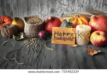 """Autumn harvest still life with pumpkins, wheat ears and lentils in sack on faded blue rustic wooden background. Paper card with greeting """"Happy Thanksgiving!"""", toned image."""