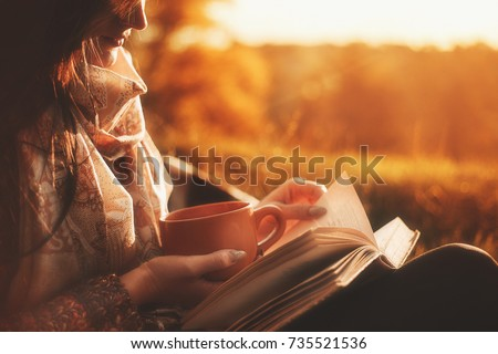 Beautiful girl in autumn forest reading a book covered with a warm blanket.a woman sits near a tree in an autumn forest and holds a book and a cup with a hot drink in her hands. Girl reading a book #735521536