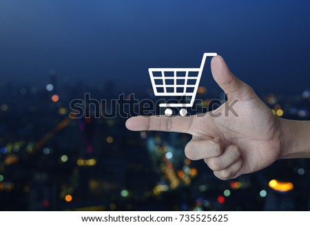 Shopping cart icon on finger over blur colorful night light city tower, Shop online concept #735525625