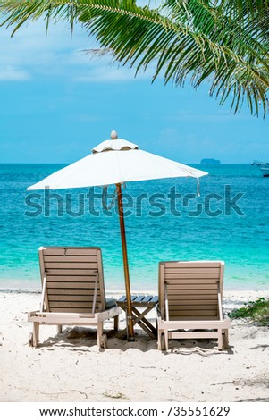 comfortable chair on the beach, modern umbrella, clear sky and sea, copy space. #735551629