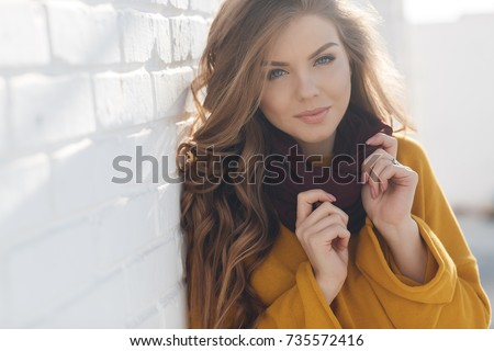 young girl in autumn colors posing near white wall smiling. Autumn woman.  Brown hair and eyes. Warm autumn. Warm spring