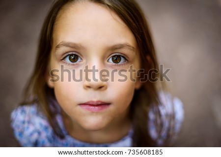 Portrait of little girl looking up at the parent outdoors. A child is looking up towards the camera outside in the woods. Shallow depth of field and soft selective focus on the eyes.
