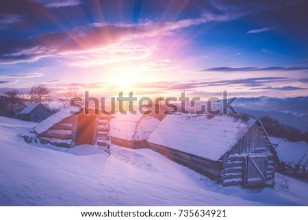 Colorful winter sunrise in the mountains. Fantastic morning glowing by sunlight. View of the snowy forest and old wooden hut cabin. Happy New Year! Filtered image:cross processed retro effect. #735634921