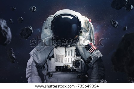 Picture of astronaut spacewalking at the awesome cosmic background. Deep space image, science fiction fantasy in high resolution ideal for wallpaper and print. Elements of this image furnished by NASA Royalty-Free Stock Photo #735649054