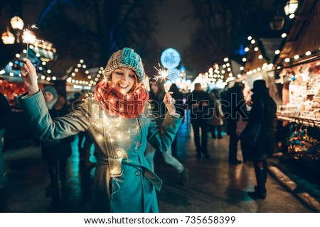 Outdoor photo of young beautiful happy smiling girl holding sparklers, posing in street. Festive Christmas fair on background. Model wearing stylish winter coat, knitted beanie hat, scarf. #735658399