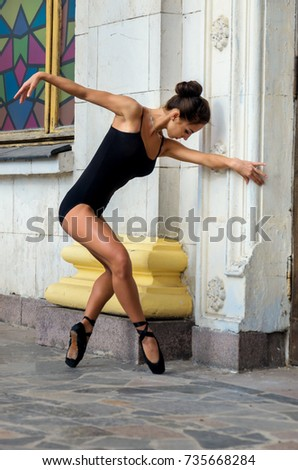 Beautiful slender sports woman dancer in a black suit and pointe dancing on a city street #735668284