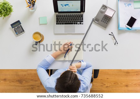 business, communication and people concept - businesswoman with laptop computer calling on phone and writing to notebook at office table #735688552